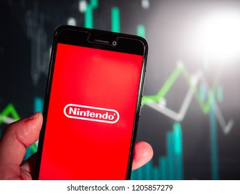 Murcia, Spain; Oct 18, 2018: Hand holding phone with Nintendo company logo with fluctuating graphic on background