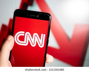 Murcia, Spain; Oct 23, 2018: CNN white logo in phone with losses graphic on background. First person view
