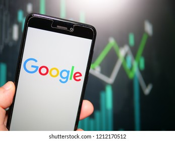 Murcia, Spain; Oct 23, 2018: Hand holding phone with Google LLC logo displayed in it with fluctuating graphic on background. First person view