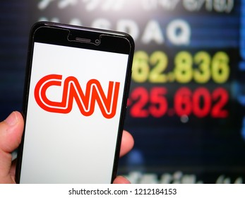 Murcia, Spain; Oct 23, 2018: CNN red logo in phone with stock exchange screen on background. First person view