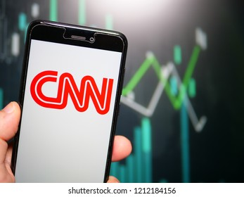 Murcia, Spain; Oct 23, 2018: Hand holding phone with CNN red logo displayed in it with fluctuating graphic on background. First person view