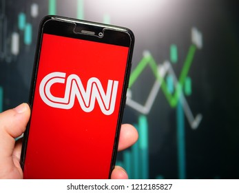 Murcia, Spain; Oct 23, 2018: Hand holding phone with CNN white logo displayed in it with fluctuating graphic on background. First person view