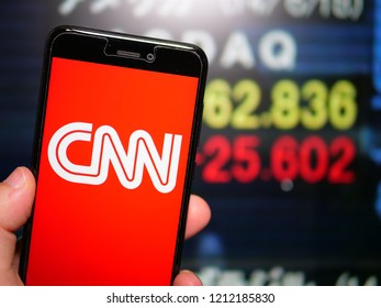 Murcia, Spain; Oct 23, 2018: CNN white logo in phone with stock exchange screen on background. First person view