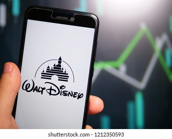 Murcia, Spain; Oct 23, 2018: Hand holding phone with Walt Disney Company logo displayed in it with fluctuating graphic on background. First person view