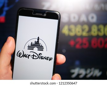 Murcia, Spain; Oct 23, 2018: Walt Disney company logo in phone with stock exchange screen on background. The Walt Disney Company is an American diversified multinational mass media conglomerate