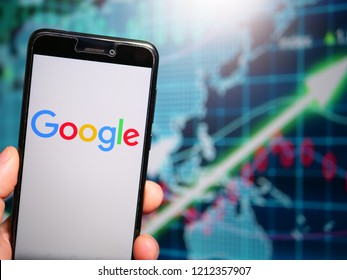 Murcia, Spain; Oct 23, 2018: Google LLC logo in phone with earnings graphic on background. Google LLC is an American multinational technology company