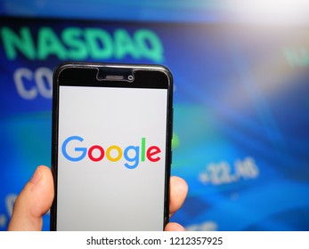 Murcia, Spain; Oct 23, 2018: Google LLC logo in phone with Nasdaq screen on background. First person view