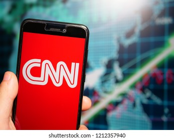 Murcia, Spain; Oct 23, 2018: CNN white logo in phone with earnings graphic on background. Cable News Network is an American news-based pay television channel