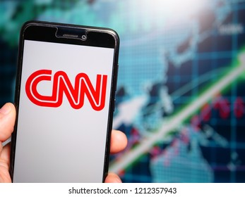 Murcia, Spain; Oct 23, 2018: CNN red logo in phone with earnings graphic on background. Cable News Network is an American news-based pay television channel