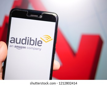 Murcia, Spain; Oct 23, 2018: Audible store logo in phone with losses graphic on background. First person view
