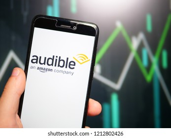 Murcia, Spain; Oct 23, 2018: Hand holding phone with Audible store logo displayed in it with fluctuating graphic on background. First person view
