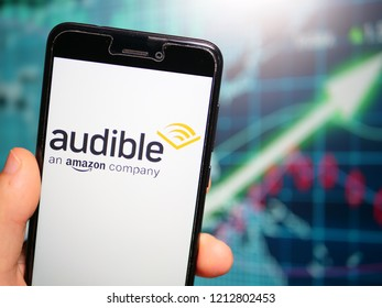 Murcia, Spain; Oct 23, 2018: Audible store logo in phone with earnings graphic on background. Audible is a seller and producer of spoken audio entertainmen