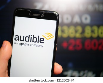 Murcia, Spain; Oct 23, 2018: Audible store logo in phone with stock exchange screen on background. First person view