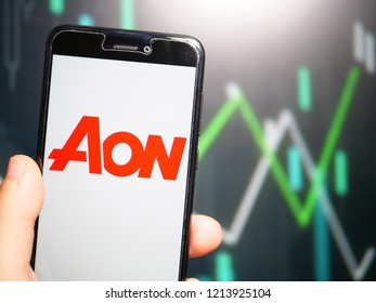 Murcia, Spain; Oct 23, 2018: Hand holding phone with Aon PLC logo displayed in it with fluctuating graphic on background. First person view