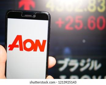 Murcia, Spain; Oct 23, 2018: Aon PLC logo in phone with New York stock exchange (NYSE) screen on background. First person view