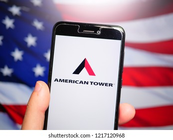 Murcia, Spain; Oct 30, 2018: American Tower Corporation (ATC) logo in phone with United States flag on background. American Tower Corporation is an American publicly held company