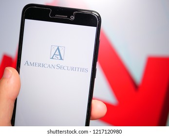 Murcia, Spain; Oct 30, 2018: American Securities LLC logo in phone with losses graphic on background. First person view