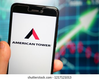 Murcia, Spain; Oct 30, 2018: American Tower Corporation (ATC) logo in phone with earnings graphic on background. American Tower Corporation is an American publicly held company