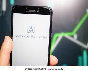 Murcia, Spain; Oct 30, 2018: Hand holding phone with American Securities LLC logo displayed in it with fluctuating graphic on background. First person view