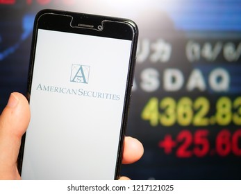 Murcia, Spain; Oct 30, 2018: American Securities LLC logo in phone with stock exchange screen on background. First person view
