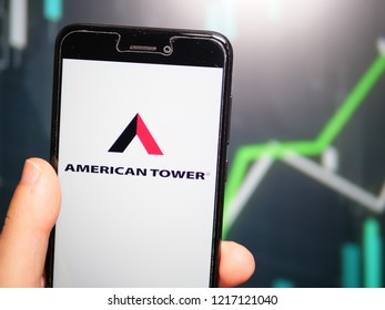 Murcia, Spain; Oct 30, 2018: Hand holding phone with American Tower Corporation (ATC) logo displayed in it with fluctuating graphic on background. First person view