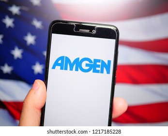 Murcia, Spain; Oct 30, 2018: Amgen logo in phone with United States flag on background. Amgen is an American multinational biopharmaceutical company