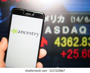 Murcia, Spain; Oct 30, 2018: Ancestry LLC logo in phone with stock exchange screen on background. First person view