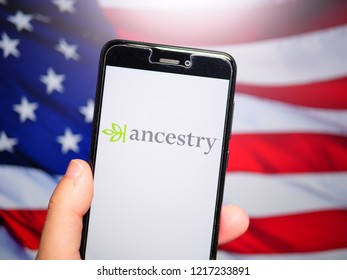 Murcia, Spain; Oct 30, 2018: Ancestry LLC logo in phone with United States flag on background. First person view