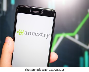 Murcia, Spain; Oct 30, 2018: Hand holding phone with Ancestry LLC logo displayed in it with fluctuating graphic on background. First person view