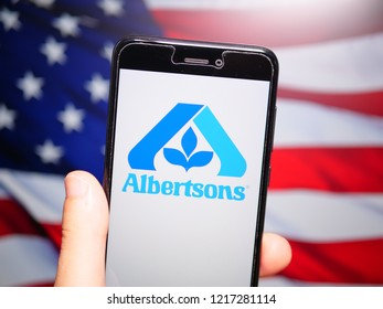 Murcia, Spain; Oct 30, 2018: Albertsons Companies LLC logo in phone with United States flag on background. Albertsons Companies LLC is an American grocery company