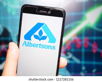 Murcia, Spain; Oct 30, 2018: Albertsons Companies LLC logo in phone with earnings graphic on background. Albertsons Companies LLC is an American grocery company