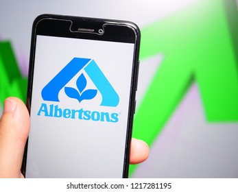 Murcia, Spain; Oct 30, 2018: Albertsons Companies LLC logo in phone with rises graphic on background. First person view