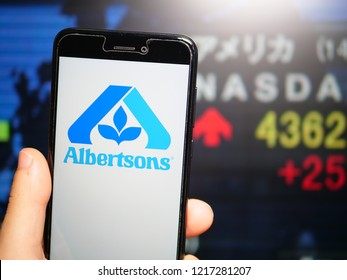 Murcia, Spain; Oct 30, 2018: Albertsons Companies LLC logo in phone with stock exchange screen on background. First person view