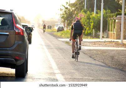 Murcia, Spain October 10, 2019: Cyclist ride bike on road along cars passing beside him keeping security distance. Man rides bicycle on the street. Bicycle rider in motorway halfway at the side road.