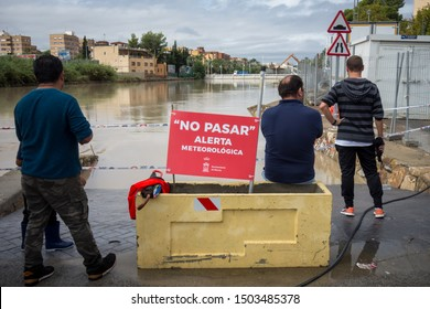 """Murcia, Spain. September 13-2019: Segura river as it passes through the city of Murcia during floods due to the atmospheric phenomenon DANA (cold drop). """"Do not pass, weather alert. Murcia City Hall"""""""