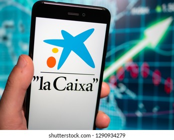 Murcia, Spian; Jan 17, 2019: Caixa Bank logo in phone with earnings graphic on background. La Caixa is currently Spain's third largest financial institution