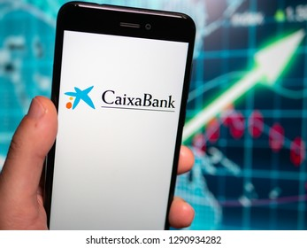 Murcia, Spian; Jan 17, 2019: Caixa Bank logo in phone with earnings graphic on background. Caixa Bank is currently Spain's third largest financial institution