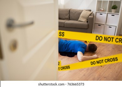 murdel and crime scene concept - dead man body in blood lying on floor and bullet sleeves fenced by police tape at home room (staged photo)
