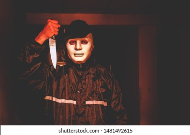 murder, kill and people concept - Criminal or murderer in black wearing a white mask holding knife inside a condo at crime scene