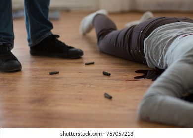 murder, kill and people concept - criminal or murderer with bleeding dead woman body lying on floor and bullet sleeves at crime scene