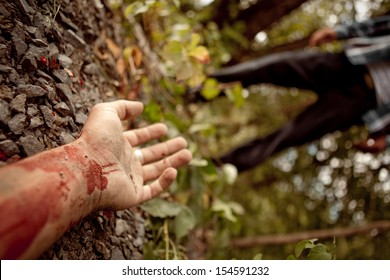 Murdered man's hand lying on the ground in the middle of the forest with the killer in the background