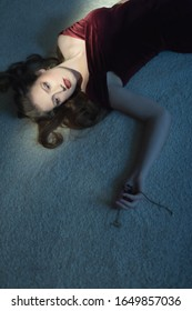 Murdered woman in red dress holding necklace in her hand lying on floor.