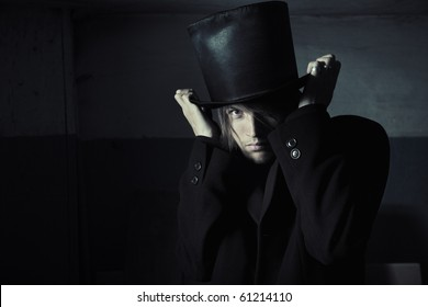 Murderer in black coat and top hat in the dark interior. Natural darkness and artistic colors added