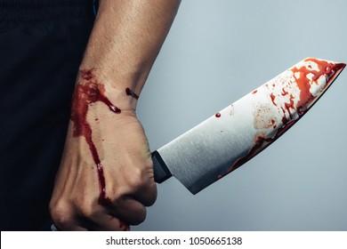 Murderer holding knife with blood splatter.