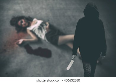 Murderer hooded man ready to attack to kill his victim that is the woman to died on ground. (Criminal low key concept)
