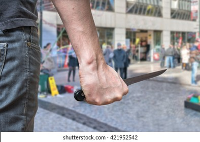 Murderer or killer is attacking with knife n public place.