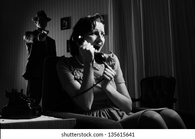 Murderess pointing the gun at a frightened woman