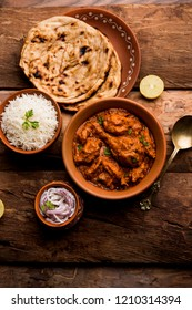 Murgh Makhani / Butter chicken tikka masala served with roti / Paratha and plain rice along with onion salad in terracotta crockery. selective focus