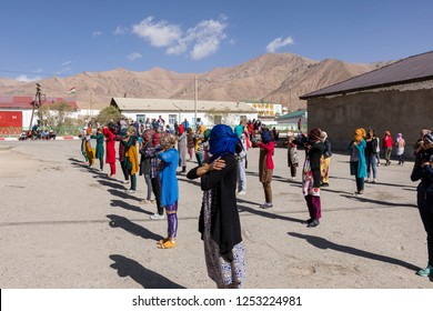Murghab, Tajikistan, August 23 2018: Kyrgyz girls and women are practicing a dance on the playground of a school in Murghab. Against the strong sunlight they have protected their faces with scarfs