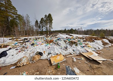 Murmansk Region, Russia - March 2018:  Elemental garbage dump on the background of the winter forest and the sky. Ecology problems in nature